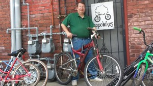 Army veteran Randy poses outside of Sopo's back door with a mountain bike he completely rebuilt at Sopo.